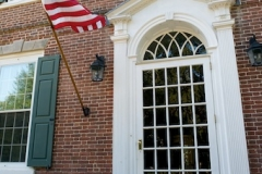 Image of the front door from the outside with the American flag